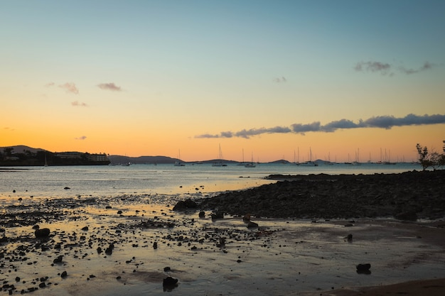 夕方の日没時にビーチと丘に囲まれた船が乗った海