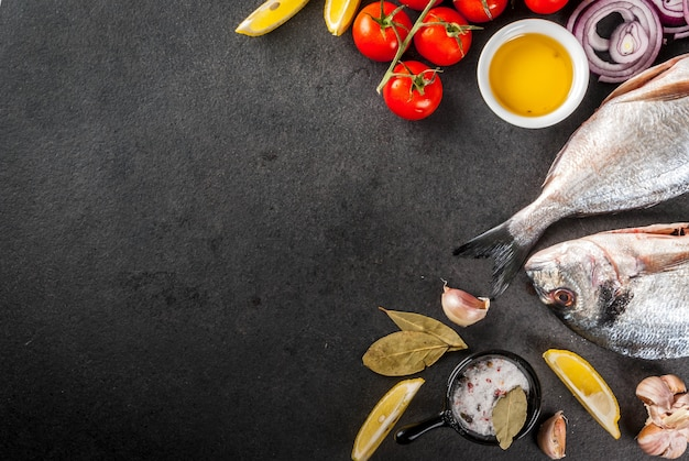 新鮮な生の有機魚ドラドseaレモントマトを調理するための材料とタマネギ塩コショウベイリーフグリーンオイル