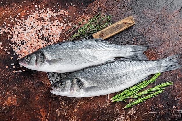 소금과 허브를 곁들인 식칼에 농어 또는 농어 신선한 생선. 어두운 배경. 평면도.