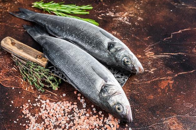 농어 또는 농어 소금과 허브와 함께 칼에 신선한 날 생선. 어두운 배경입니다. 평면도.