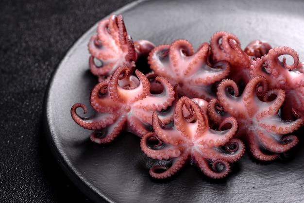 Морепродукты детский салат из осьминога в черной тарелке. средиземноморская кухня для гурманов