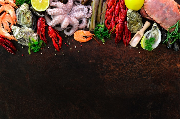 Seafood background - fresh mussels, molluscs, oysters, octopus, razor shells, shrimps, crab, crawfish, crayfish, seaweed, lemon, spices.