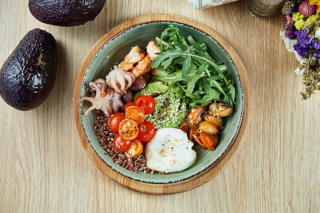 Seafood bowl with avocado, quinoa, octopus, mussels, cherry tomatoes and poached egg. buddha bowl with healthy and balanced food. top view, flat lay