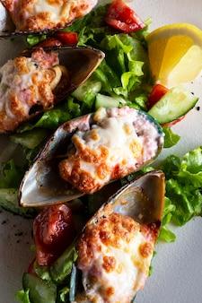 해물. 홍합 조개. 하얀 접시에 치즈, 양상추, 레몬을 넣은 녹색 껍질에 구운 홍합