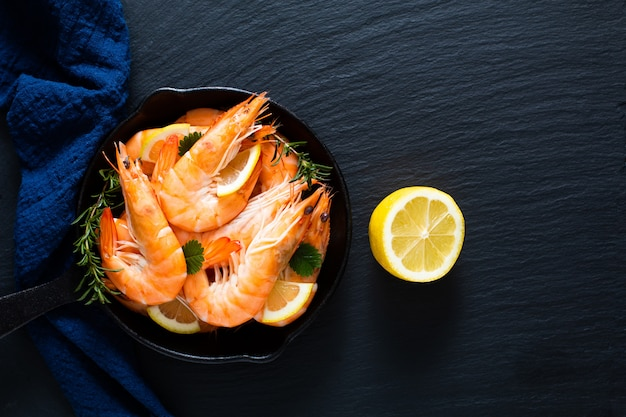 Seafood concept ocean king prawns cooked in skillet iron cast on black slate stone with blue napkins