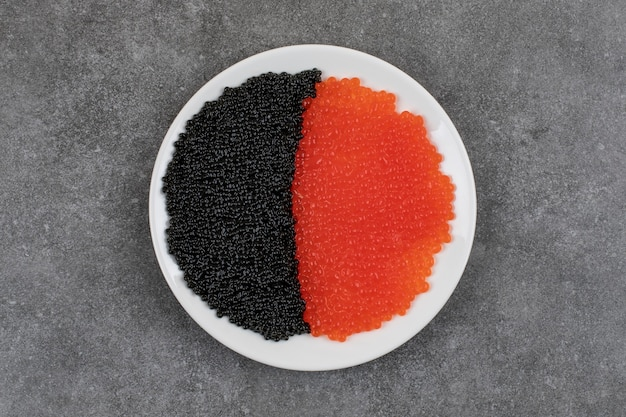 Seafood concept. red and black caviar on white plate.