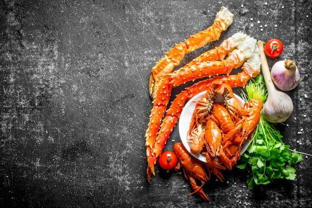Морепродукты. приготовленные раки и крабы с чесноком, петрушкой и помидорами на черном деревенском столе