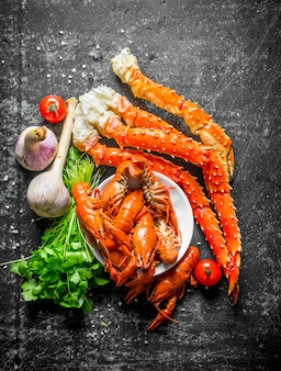 Seafood. cooked crayfish and crab with garlic, parsley and tomatoes on dark rustic table