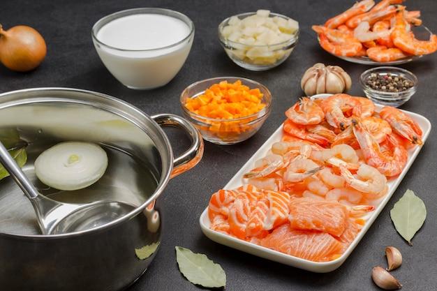 クラムチャウダーのスープを調理するためのシーフード、クリーム、野菜の食材。