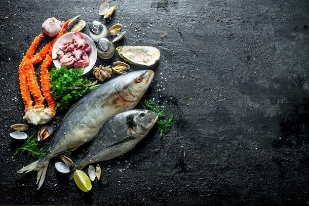 Морепродукты. разные рыбы с устрицами, крабами и осьминогами. на черном деревенском