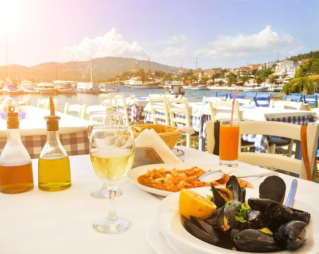 太陽の光とギリシャの海辺のギリシャ料理レストランでのシーフードディナー