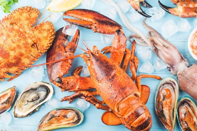 Ужин из морепродуктов, ужин из морепродуктов со свежими лобстерами, крабами, мидиями и устрицами в качестве фона