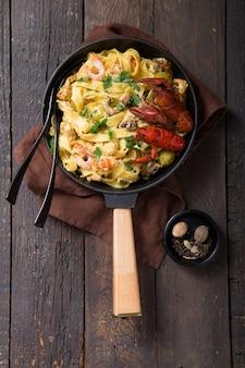 Паста феттучини с морепродуктами, раками, креветками осьминога, на каменной сковороде. блюдо для гурманов