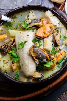 Seafood fish soup in clay bowls served with cold white wine