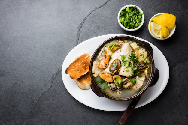 Seafood fish soup in clay bowls served with lemon and coriander.