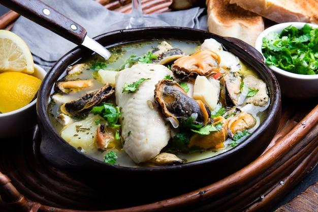 Рыбный суп из морепродуктов в глиняных мисках с лимоном и кориандром.