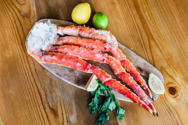 調理用シーフード、カニ、海の爬虫類の肉、モルスキー、レモン、前菜、グルメ料理、ロブスター、レストラン、ボードの上に横たわるカニ