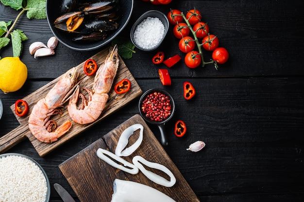 Морепродукты для традиционной испанской паэльи на черном деревянном фоне, плоская планировка с копией пространства