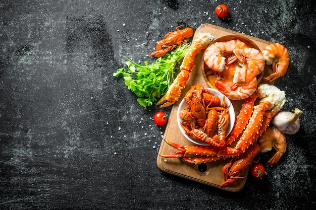 Морепродукты. ароматные креветки, раки и крабы на деревянной доске с зеленью и помидорами черри. на темном деревенском