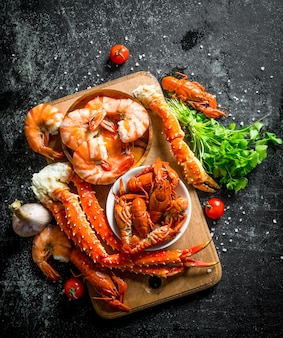 Seafood. fragrant shrimp, crayfish and crab on a wooden board with herbs and cherry tomatoes.