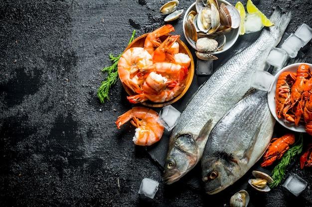 Морепродукты. свежая рыба с креветками, раками и устрицами на каменной доске.