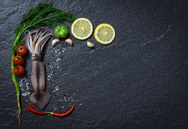 Seafood fresh squid raw ocean gourmet dinner with herbs and spices with lemon tomato
