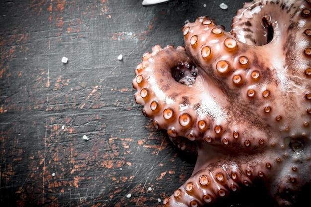Морепродукты. только что пойманный осьминог на темном деревянном столе