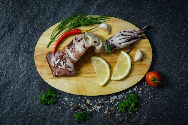 Seafood grilled squid with herbs and spices lemon tomato chilli garlic and dill  on cutting board
