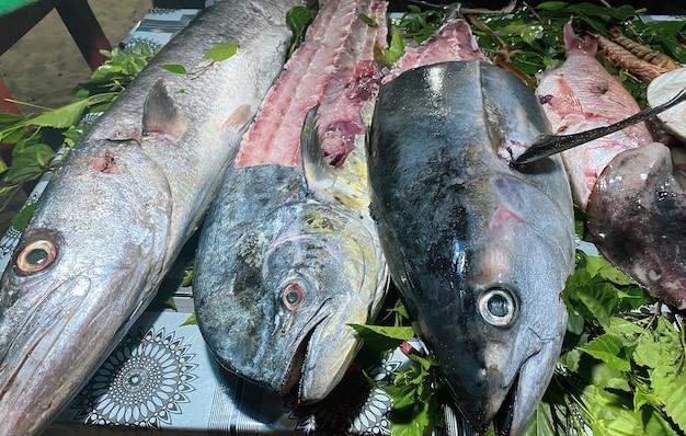 アフリカのリゾートタウンにあるレストランのテーブルには、さまざまな種類の魚を含むシーフードが並んでいます。旅行のコンセプト。