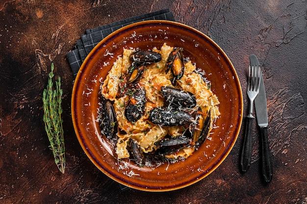 소박한 접시에 홍합과 토마토 소스를 곁들인 해산물 마팔딘 파스타. 어두운 배경입니다. 평면도.