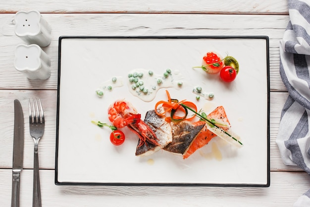 Seafood mix on white plate with cutlery