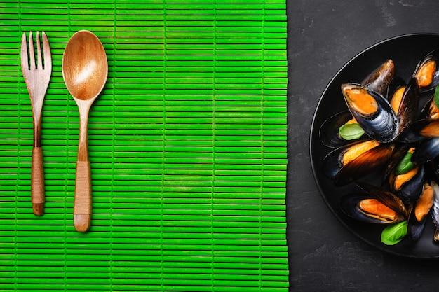 해산물 홍합과 바질 잎은 대나무 매트와 돌 테이블에 있는 검은 접시에 있습니다. 평면도.