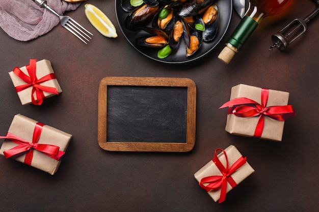 Мидии из морепродуктов и листья базилика в черной тарелке с вилкой, ножом, классной доской и подарочными коробками на полотенце и ржавом фоне. вид сверху с местом для текста.