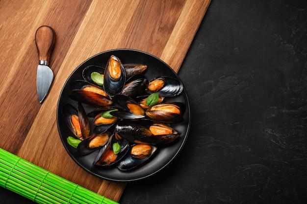 レモン、木の板と石のテーブルの上のナイフと黒いプレートのシーフードムール貝とバジルの葉。テキストの場所を含む上面図。