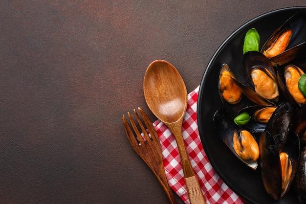 Мидии из морепродуктов и листья базилика в черной тарелке с полотенцем, деревянной ложкой и вилкой на ржавой предпосылке. вид сверху.