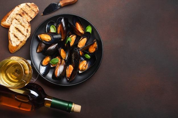 Мидии из морепродуктов и листья базилика в черной тарелке с винной бутылкой, рюмкой, ломтиками хлеба и ножом на ржавом фоне. вид сверху.