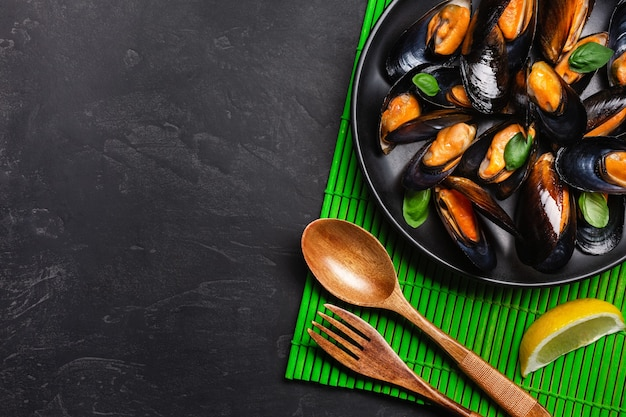 Seafood mussels and basil leaves in a black plate on bamboo mat and stone table. top view.