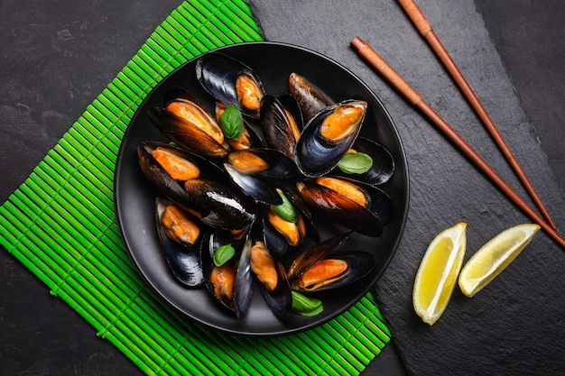 Seafood mussels, basil leaves in a black plate with lemon and chopsticks on green bamboo mat and stone table. top view.