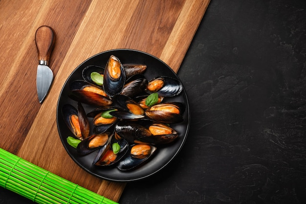 Seafood mussels and basil leaves in a black plate with lemon, knife on wooden board and stone table. top view with place for your text.
