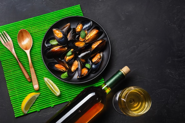 Seafood mussels, basil leaves in a black plate with wine bootle, wineglass, lemon, wooden spoon and fork on green bamboo mat and stone table. top view.