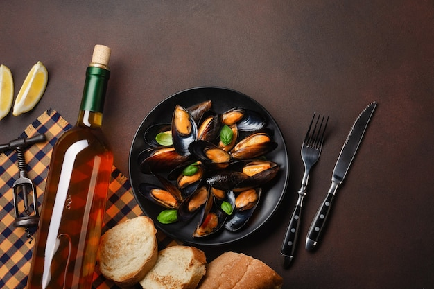 Seafood mussels and basil leaves in a black plate with wine bottle, corkscrew, bread slice, fork and knife on towel and rusty background. top view with place for your text.