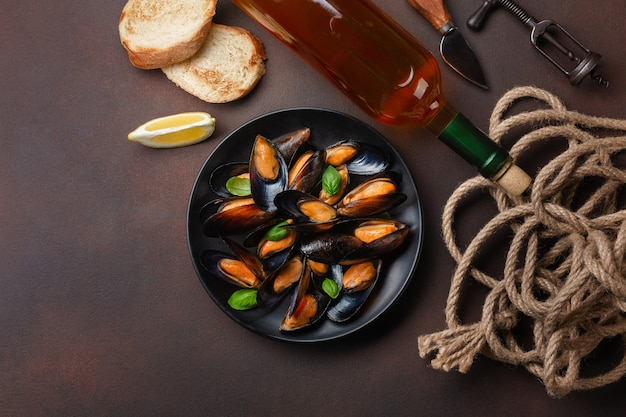 Seafood mussels and basil leaves in a black plate with wine bottle, corkscrew, rope, bread slice, fork and knife on rusty background. top view.