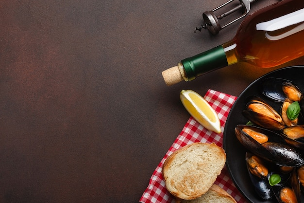 Seafood mussels and basil leaves in a black plate with wine bottle and corkscrew on towel and rusty background. top view with place for your text.