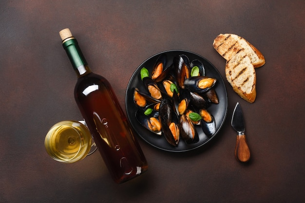 Seafood mussels and basil leaves in a black plate with wine bottle, wineglass, bread slices and knife on rusty background. top view.