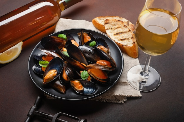 Seafood mussels and basil leaves in a black plate with wine bottle, wineglass, corkscrew, bread slices, burlap on rusty background. top view.
