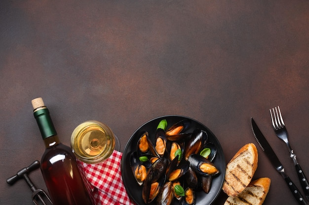 Seafood mussels and basil leaves in a black plate with wine bottle, wineglass, corkscrew, fork and knife on towel and rusty background. top view with place for your text.