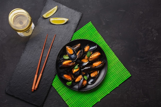 Seafood mussels, basil leaves in a black plate with wineglass, lemon and chopsticks on green bamboo mat and stone table. top view.
