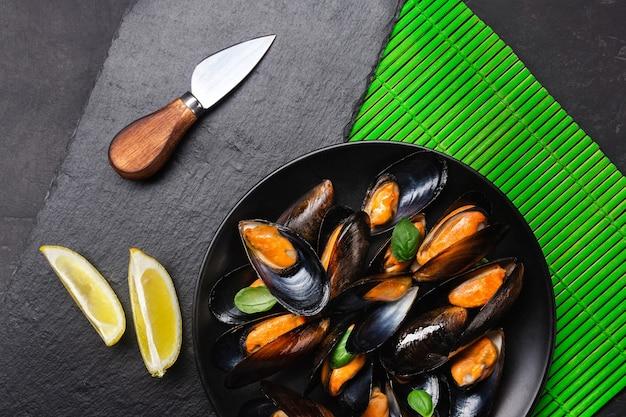 緑の竹マットと石のテーブルにレモンとナイフを添えた黒いプレートにシーフードムール貝、バジルの葉。上面図。