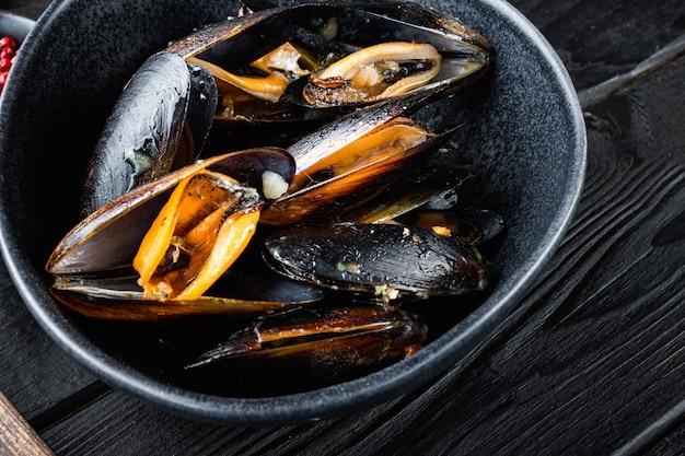 검은 나무 테이블 위에 검은 그릇에 해산물 홍합, 음식 사진.