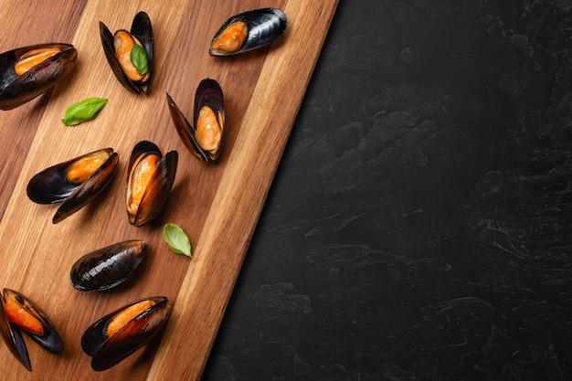 Мидии из морепродуктов с листьями базилика на деревянной доске и каменном столе. вид сверху с местом для текста.